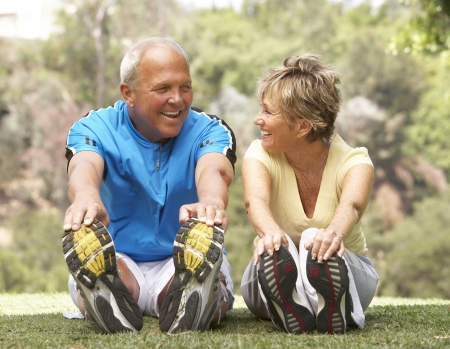 senior couples: Senior Couple Exercising In Park Stock Photo