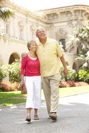 Senior Couple Walking Through City Street photo