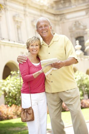 Senior Couple Walking Through City Street With Map photo