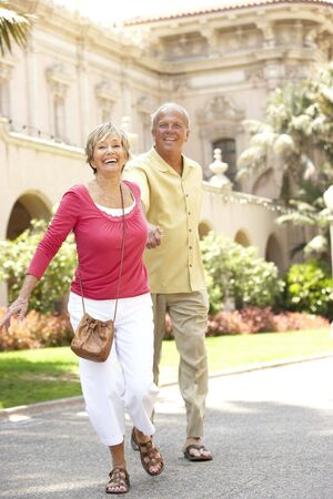 Senior Couple Walking Through City Street photo