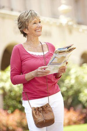 Senior Woman Walking Through City Street With Map photo