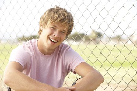 teenage boy: Teenage Boy Sitting In Playground Stock Photo