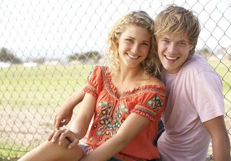 Teenage Couple Sitting In Playground photo