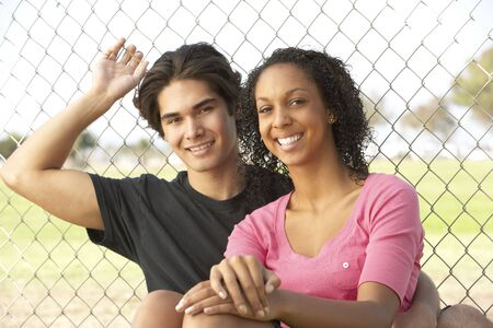 Teenage Couple Sitting In Playground photo