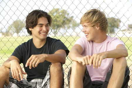 19 year old boy: Group Of Teenagers Sitting In Playground Stock Photo