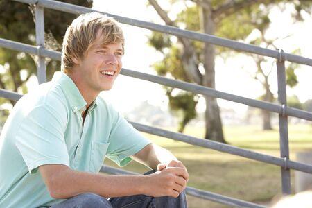 Teenage Boy Sitting In Playground photo