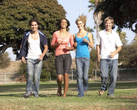 Group Of Teenagers Running In Park photo