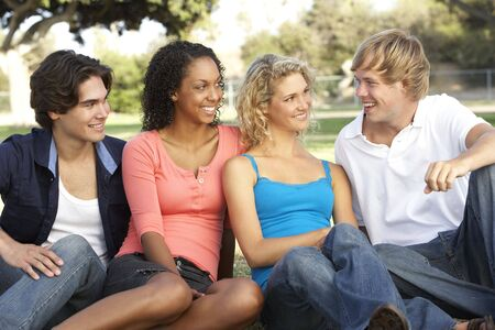 Group Of Teenagers Sitting In Playground photo