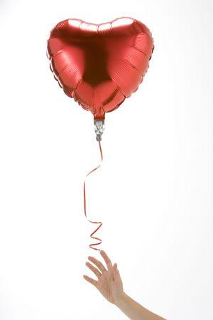 helium: Hand Letting Go Of Heart Shaped Balloon Stock Photo
