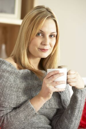 Portrait Of Young Woman Sitting On Sofa With Cup Of Coffee photo