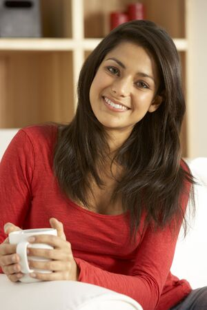 indian girl: Young Woman Sitting On Sofa With Cup Of Coffee Stock Photo