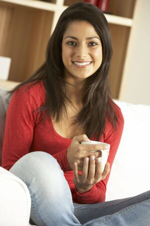 indian style sitting: Woman sitting at home drinking coffee Stock Photo