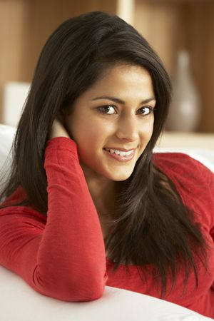 indian style sitting: Portrait Of Young Woman Relaxing At Home