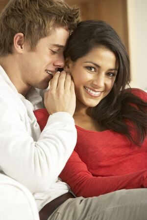 whispering: Young Couple Sitting On Sofa