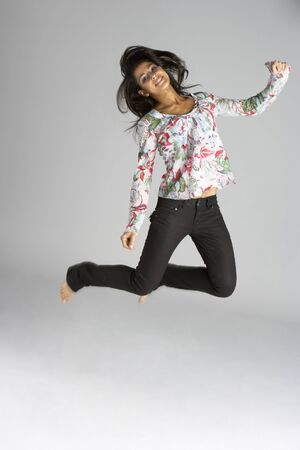 Studio Portrait Of Young Woman Jumping In Air photo