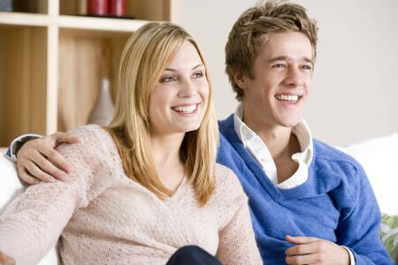 Young Couple Sitting On Sofa Together Watching TV photo