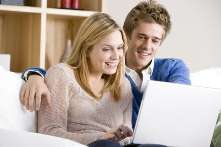 Young Couple Sitting On Sofa Using Laptop photo