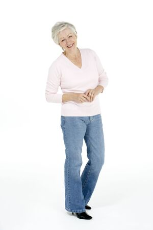 Full Length Studio Portrait Of Smiling Senior Woman