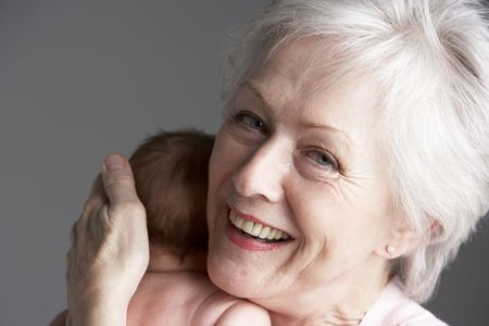 Studio Shot Of Grandmother Cuddling Granddaughter photo