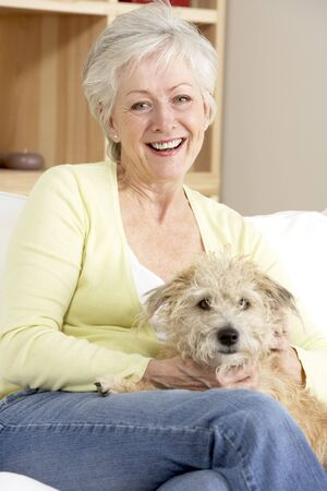older woman smiling: Senior Woman Holding Dog On Sofa Stock Photo