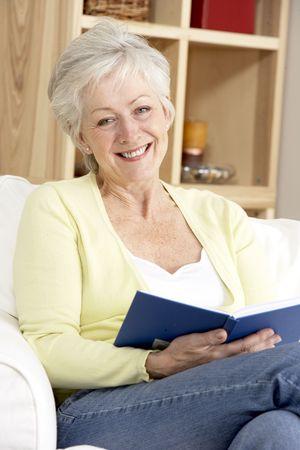 mujer leyendo libro: Libro de lectura de mujer senior en casa