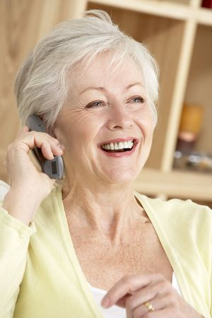 Senior Woman Using Phone At Home photo