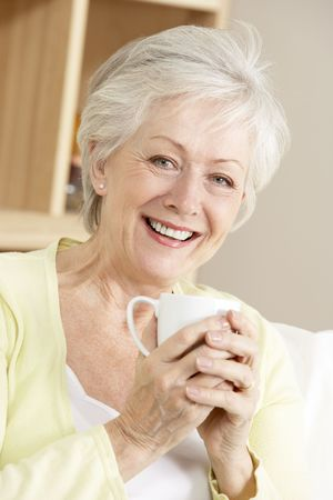 mujeres mayores: Mujer Senior Enjoying Hot Drink At Home Foto de archivo