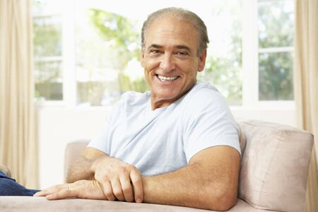Senior Man Relaxing In Chair At Home photo
