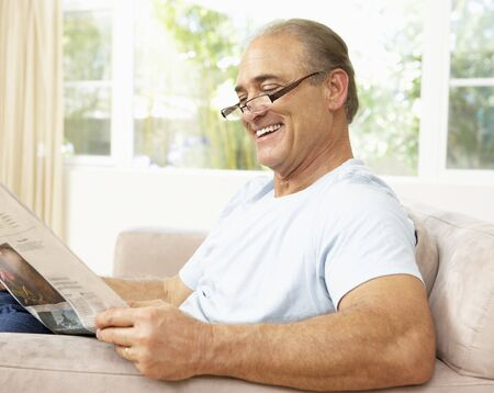 Senior Man Reading Newspaper At Home photo