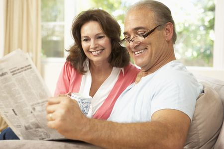 reading room: Senior Couple Reading Newspaper At Home Stock Photo