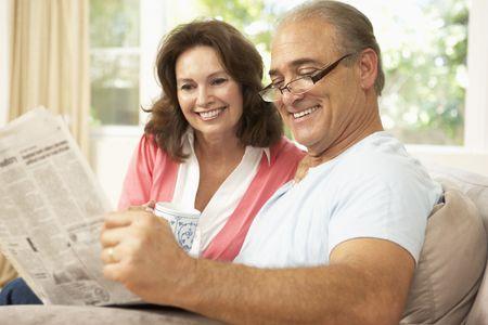 two people talking: Senior peri�dicos de lectura de pareja en el hogar