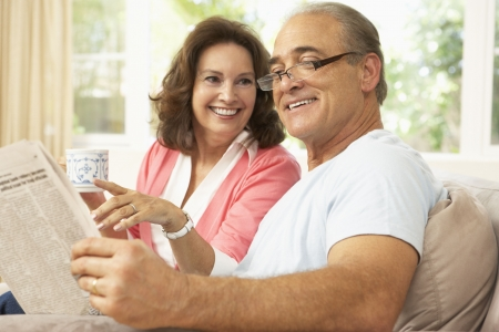 Senior Couple Reading Newspaper At Home photo