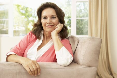 Senior Woman Relaxing In Chair At Home photo