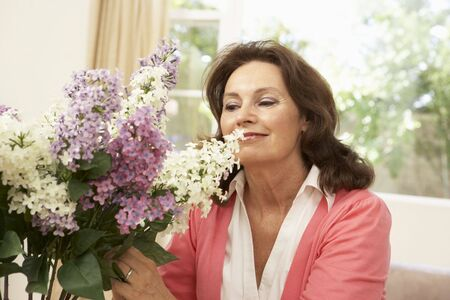 Senior Woman At Home Arranging Flowers photo