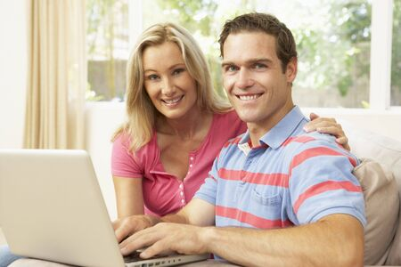 Young Couple Using Laptop At Home photo