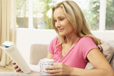 woman reading: Woman Reading Book With Drink At Home