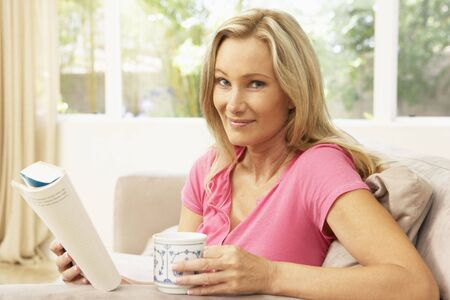Woman Reading Book With Drink At Home photo