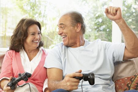 Senior Couple Playing Computer Game At Home photo