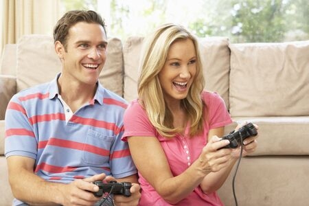 Young Couple Playing Computer Game On Sofa At Home photo