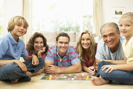 game room: Family Playing Board Game At Home With Grandparents Watching Stock Photo