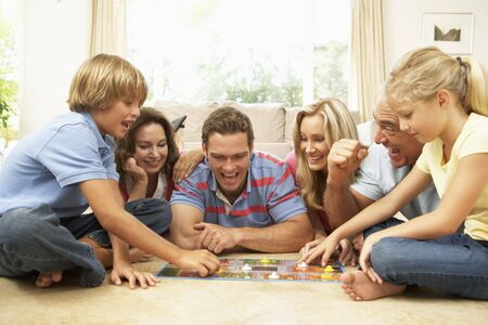 board room: Family Playing Board Game At Home With Grandparents Watching Stock Photo