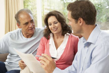 financial advice: Senior Couple With Financial Advisor At Home