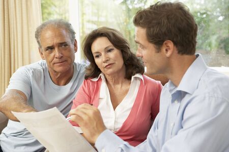Senior Couple With Financial Advisor At Home photo