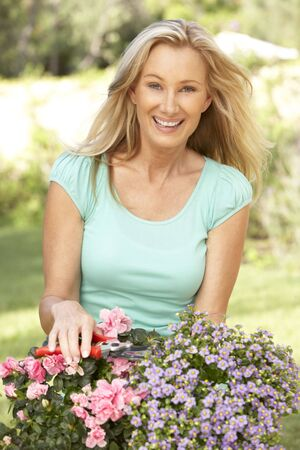 middle age woman: Young Woman Gardening Stock Photo