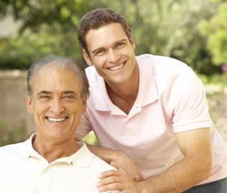padre e hijo: Senior Man abrazos a son adulto  Foto de archivo