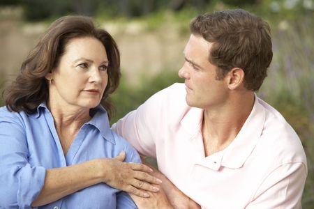 comforted: Senior Woman Being Comforted By Adult Son Stock Photo