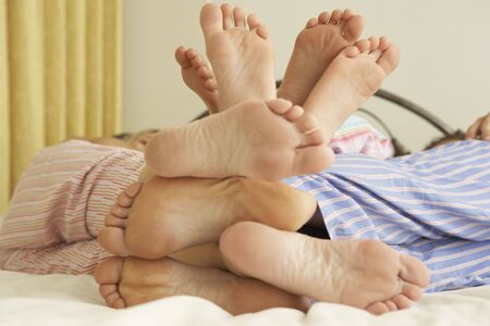 Close Up Of Familys Feet Relaxing On Bed At Home photo