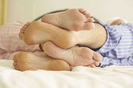 Close Up Of Couple's Feet Relaxing On Bed At Home Stock Photo - 6452842