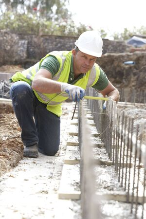 Construction Worker Laying Foundations photo