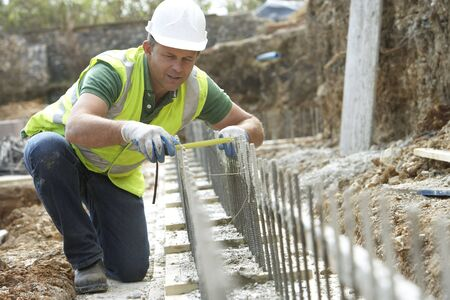 construction safety: Construction Worker Laying Foundations